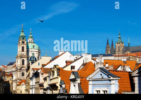 Prague, St. Nicolas church, St. Vitus Cathedral and and orange tiled roofs on a bright day. Space for your text - Stock Photo