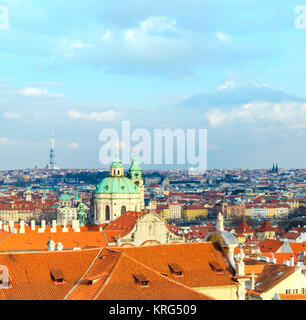 St. Nicolas church and and roofs of Prague on a bright day - Stock Photo