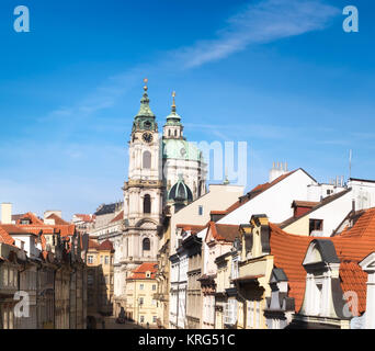 St. Nicolas church and and roofs of Prague on a bright day, panoramic image - Stock Photo