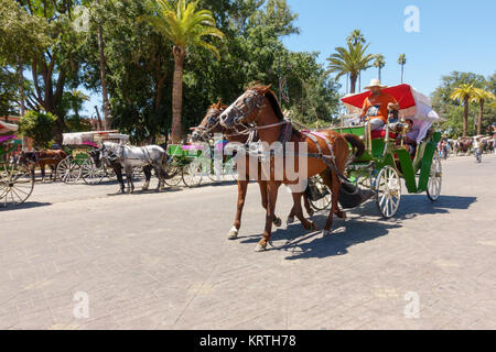 Marrakech, Morocco - May 12, 2017: Horse drawn carriage taking tourists for a ride on the road leading to Jemaa - Stock Photo