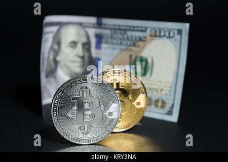 Bitcoins versus dollars concept with metal coins and paper banknote on black background - Stock Photo