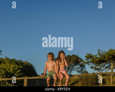 A young boy and girl sitting on a fence - Stock Photo