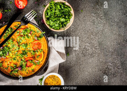 Indian food recipes, Masala Omelette with fresh vegetables - tomato, hot chili pepper, parsley, dark stone background, - Stock Photo