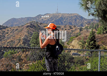 A woman tourist wearing a baseball cap taking a selfie with ipod phone and Hollywood sign at Griffith Park, Los - Stock Photo