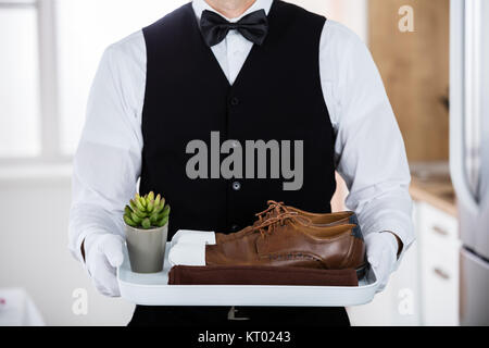 Butler Carrying Pair Of Brown Shoes - Stock Photo