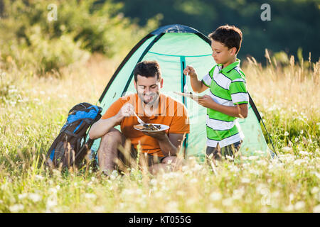 Father and son are camping in nature. They are eating. - Stock Photo
