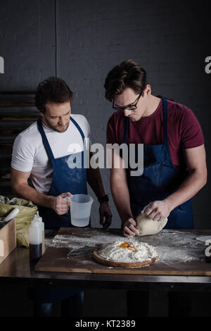 Bakers preparing dough - Stock Photo