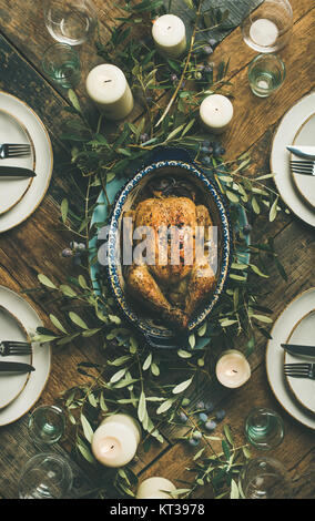 Flat-lay of whole roasted chicken in tray for Christmas eve celebration, plates, glasses and candles over rustic - Stock Photo