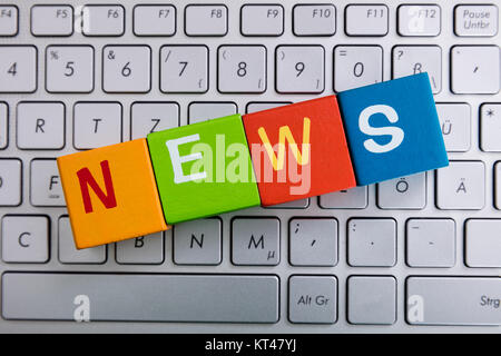 News Text On Cubes Over Laptop - Stock Photo