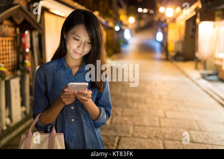 Woman sending sms on cellphone - Stock Photo