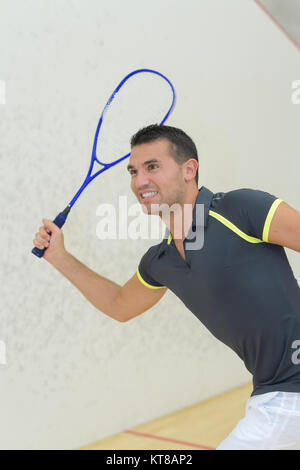 professional player playing tennis in indoor court - Stock Photo