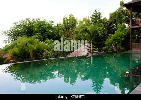 Villa Infinity Pool. A Balinese infinity pool overlooking tropical forest - Stock Photo