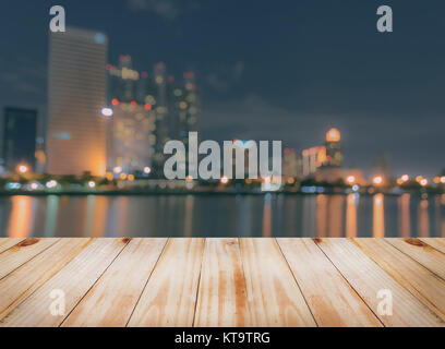 Empty wooden table with blurred city skyline background  at night - Stock Photo