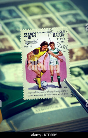 Tweezers hold a postage stamp printed by Cambodia, Color edition on topic of Football World Cup 1986 in Mexico, - Stock Photo