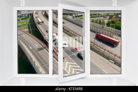Loud road traffic noise immission from driving cars in opened one frame of pvc window - Stock Photo