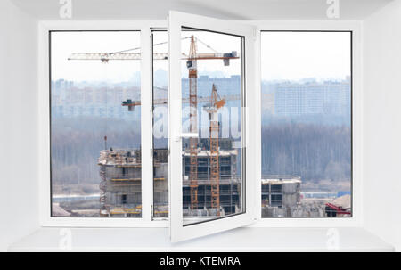 Loud construction site noise immission in opened one frame of white pvc window, view through - Stock Photo