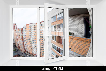 Triple-casement pvc window with view at the facade of multi-apartment house with balconies - Stock Photo