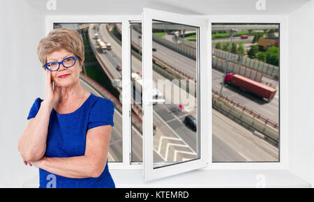 Happy smiling senior woman standing inside near threefold pvc window pane with hoisy highway with cars on background - Stock Photo