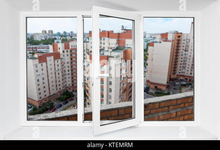 View through the pvc window frame on balcony on high floor at multi-apartment buildings - Stock Photo