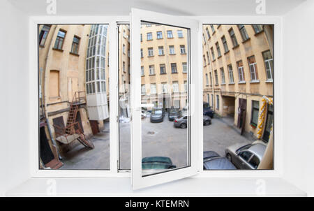 View through the pvc window frame on first floor at the narrow quadrangle with parked cars - Stock Photo
