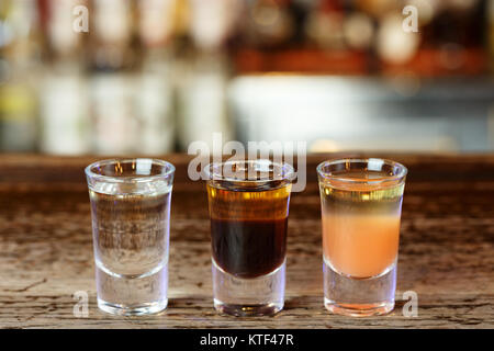 Different strong alcoholic cocktails shots in a nightclub on the bar counter - Stock Photo