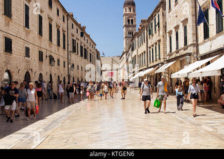 Many tourists walk on one of the major streets (Stradun) in Dubrovnik old town on sunny summer day. - Stock Photo