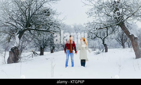 Peaceful beautiful couple holding hands and walking along the path along the winter forest covered with fluffy snow - Stock Photo