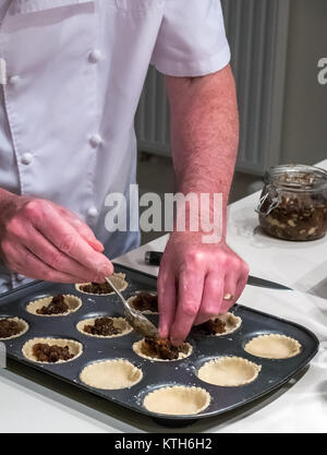 Older man in chef whites filling mince pie cases ready for baking at Christmas time in a kitchen - Stock Photo