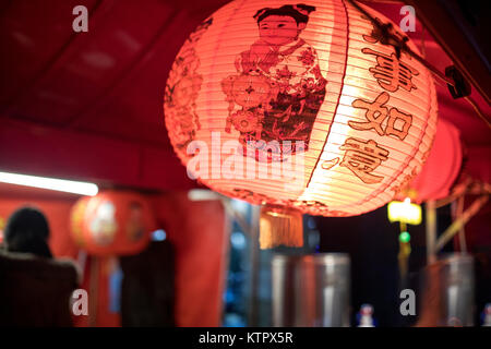 Close up of a Chinese lamp or lantern lit up and hanging outside a noodle bar at a street festival in the UK - Stock Photo