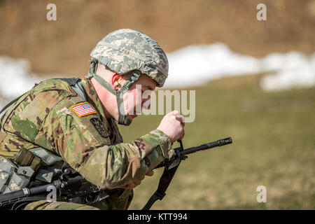 U.S. Army Spc. Mitchell Cooper adjusts his M4's front sights before shooting a weapon qualification during the New - Stock Photo