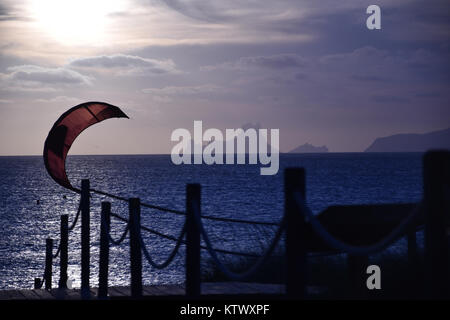 A kite-surf sail flying while sun goes down on the Mediterranean Sea with a cloudy sky and Es Vedrà on the background - Stock Photo