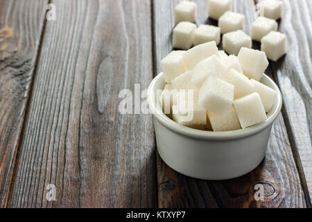 White sugar in bowl on wooden background. Selective focus, horizontal. A few sugar cubes are near the full glass - Stock Photo