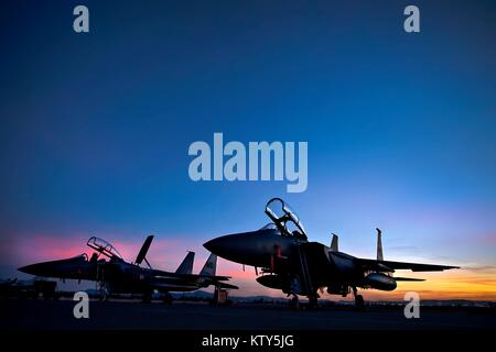 The sun sets over two F-15E Strike Eagle jet fighter aircraft on the runway at the Nellis Air Force Base at night - Stock Photo