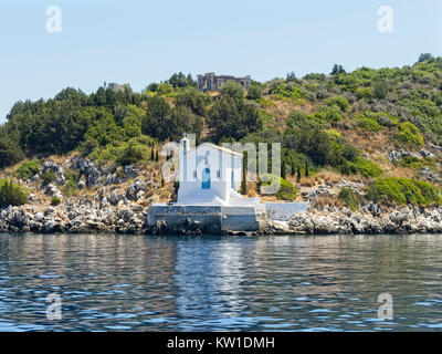 A small white church stands on rocks ot the waters edge on the island of Ithaka - Stock Photo