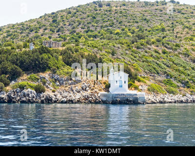 At the bottom of a high wooded hill a white church stands on rocks on the shores of the Ionian sea on the island - Stock Photo