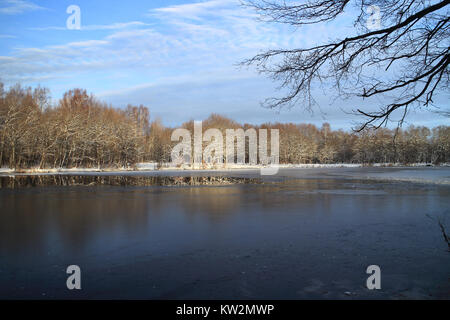 beautiful winter landscape the river is icebound, the trees under the snow are lit by the setting sun - Stock Photo