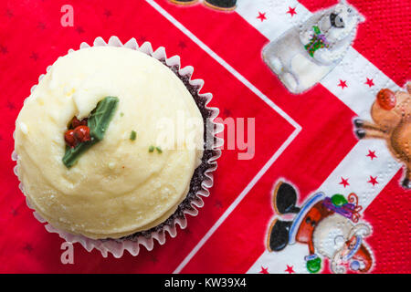 Christmas Pudding Red Velvet muffin on Christmas serviette - Stock Photo