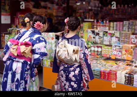 Japanese girls in bright Yukatas stopped by a souvenir store with traditional Kyoto treats and desserts on Matsubara - Stock Photo