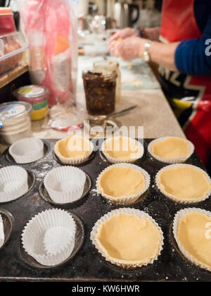 Making Mince Pies: A lady making mince pies. Circles of pastry are put into cupcake cases in a baking tin. 7 of - Stock Photo