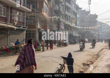 People in cold dusty streets of wintertime Kathmandu, Nepal - Stock Photo