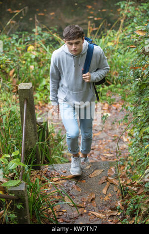 Teenage boy walking up concrete steps near a canal on an autumn day - Stock Photo