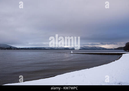 Snow covered landscape of Loch Lomond the largest freshwater source in the UK - Stock Photo