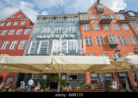 Restaurant at Nyhavn, a 17th century harbor district in the center of Copenhagen and currently a popular waterfront - Stock Photo
