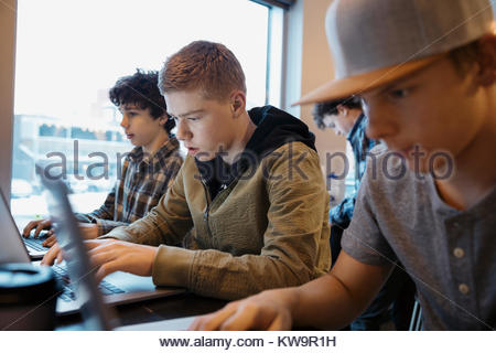 Serious,focused high school boy students studying at laptops in cafe - Stock Photo