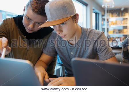 Serious,focused high school boy students studying at laptop - Stock Photo