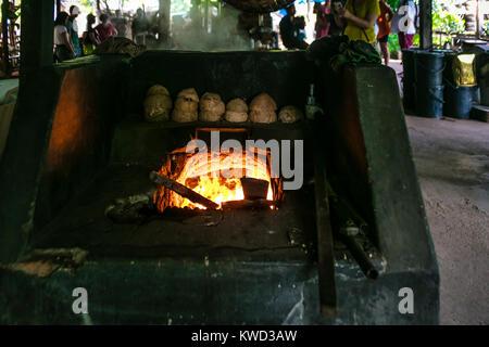 Wood fired burner for evaporating coconut sugar sap at plantation, Tambon Kradangnga, Samut Songkhram, Thailand. - Stock Photo