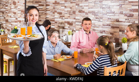 friendly young waitress warmly welcoming guests to comfortable family cafe - Stock Photo