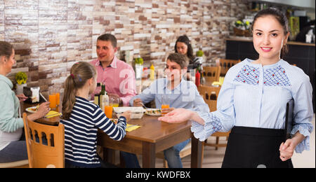 Young smiling wairtess with menu is inviting in cafe. - Stock Photo