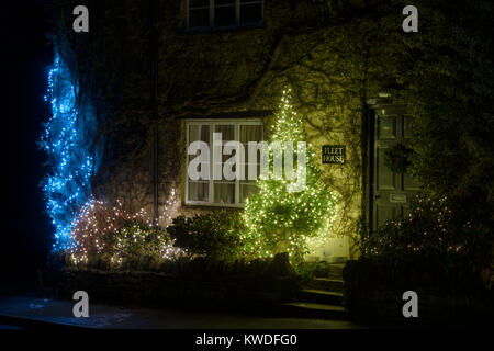 Christmas tree with lights at night outside a cottage in Greatworth, Northamptonshire, England - Stock Photo
