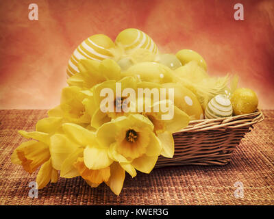 Still life of easter basket decorated with flowers and eggs on wicker table mat against pink textured wallpaper - Stock Photo